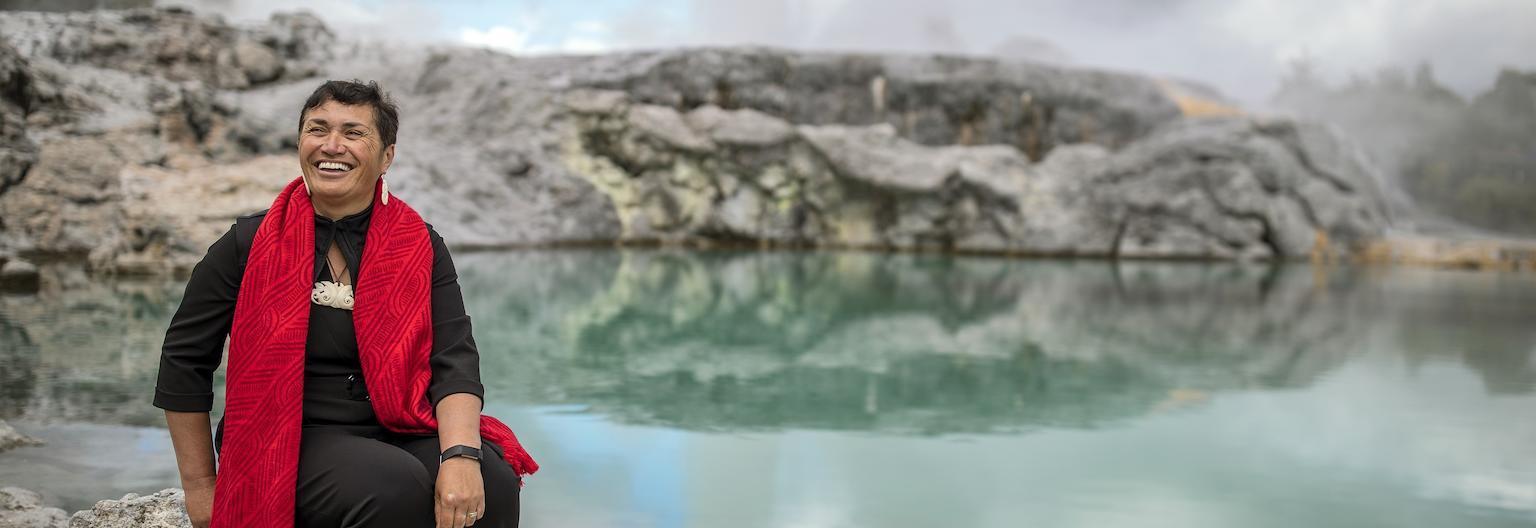 A Maori host smiling lakeside in geothermal Rotorua