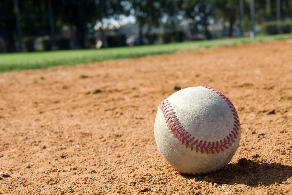 A baseball and glove laying on the baseball field
