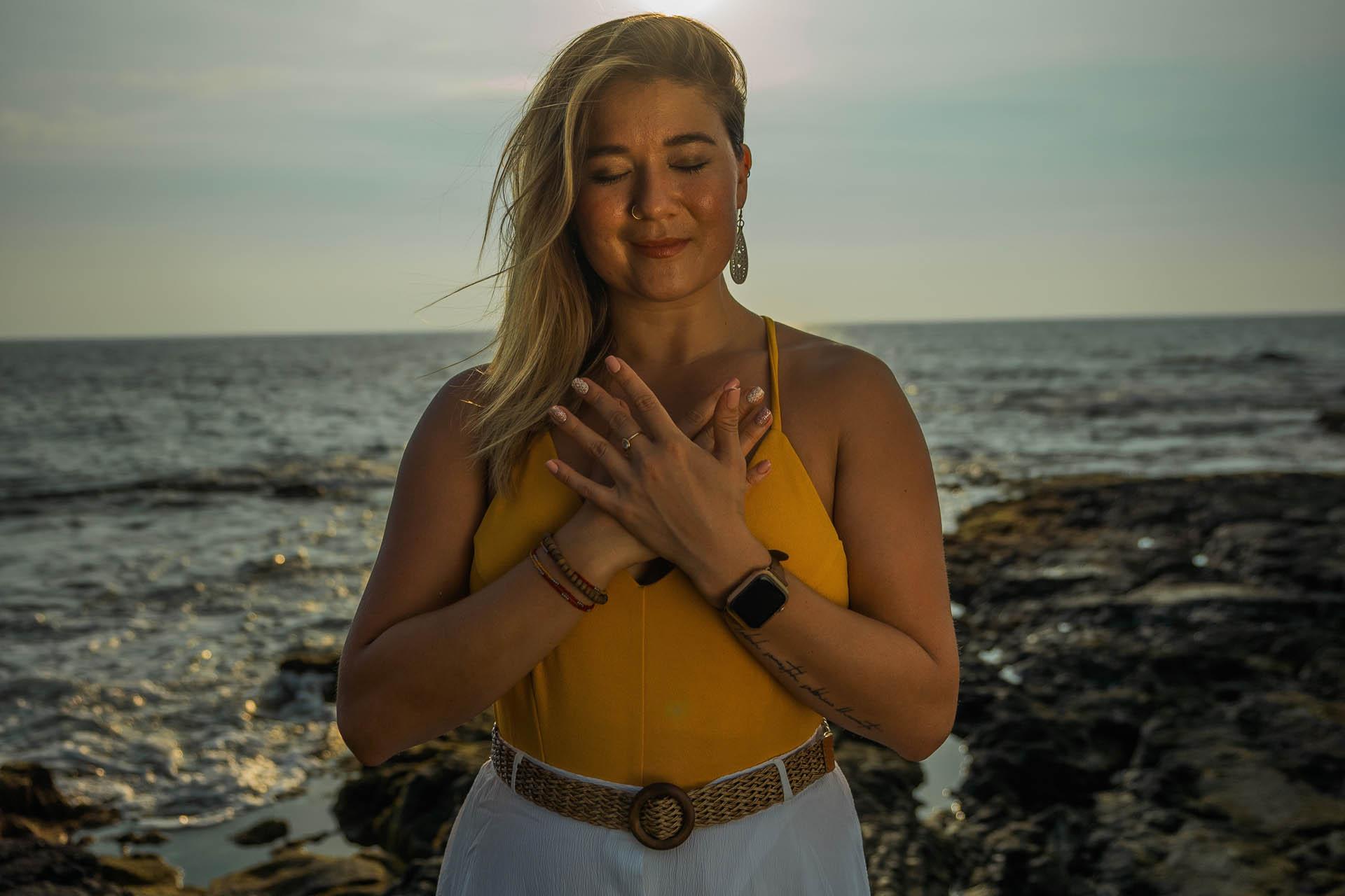 Woman standing in front of ocean with hands over heart.