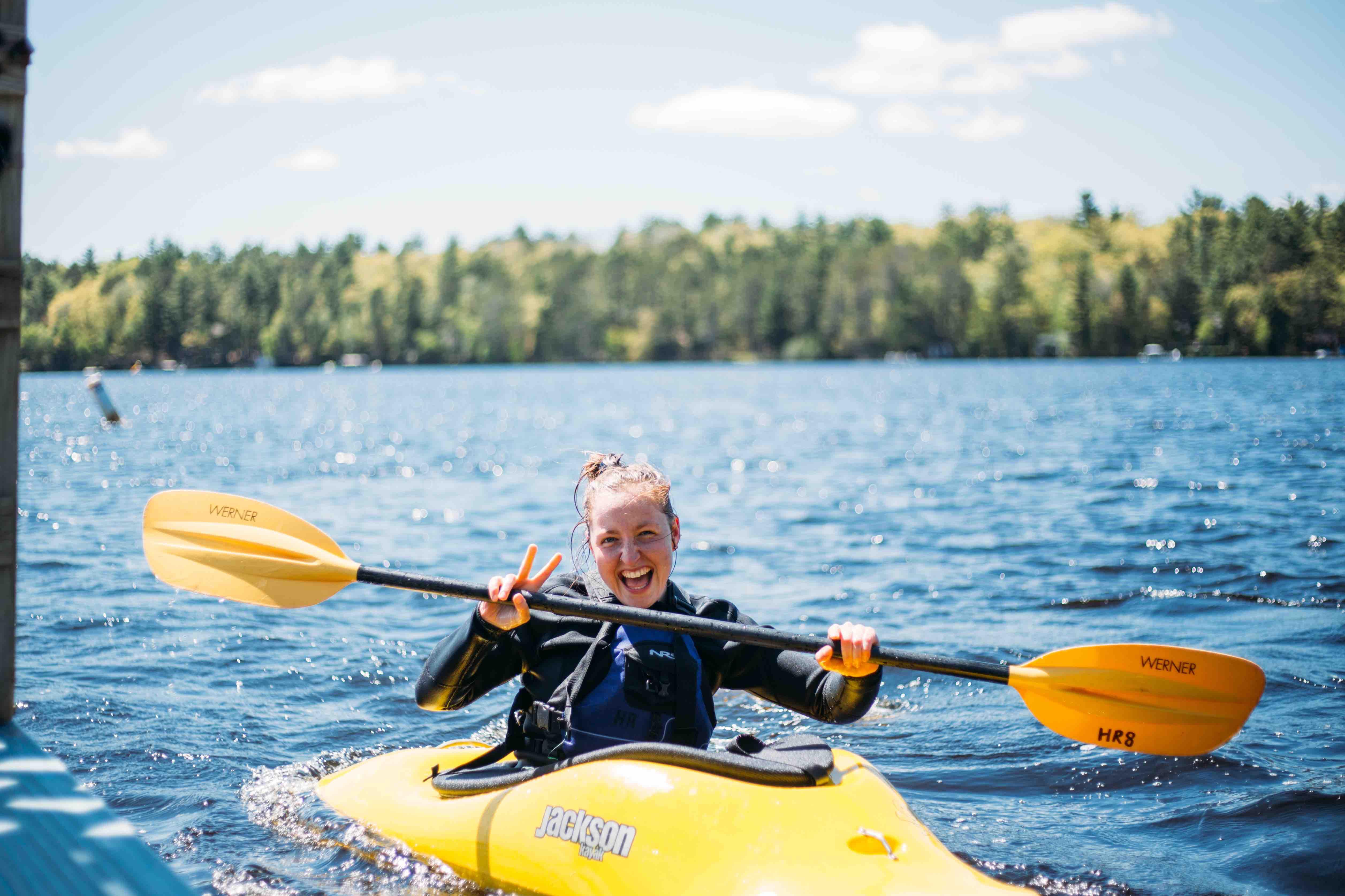 girl kayaks in a lake